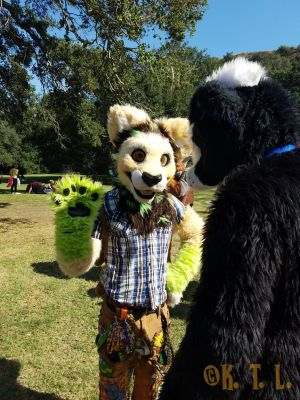 Fursuiter Wildchild waving to the camera, standing with another fursuiter