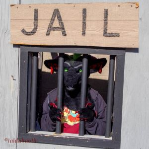Demon fursuit standing behind bars at Julian's Oktoberfest
