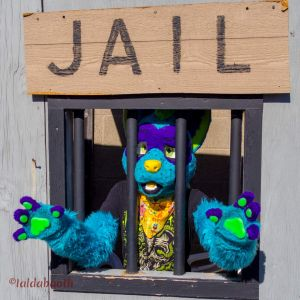 Fursuiter standing behind prop bars, pleading with those that walk by