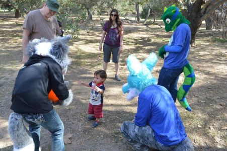 Fursuiters surround a curious child photo courtesy PonyQuest