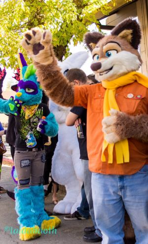Fursuiters waving while standing in the shade