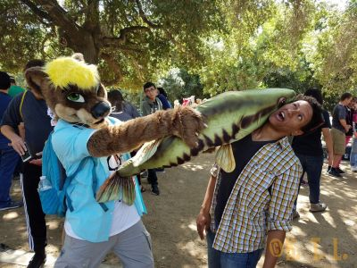 Fursuiter Cinnamon Otter playfully slapping another attendee with his soft plush fish