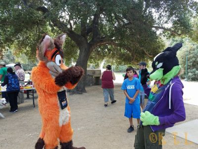 fursuiters standing around, with a child standing off to the side