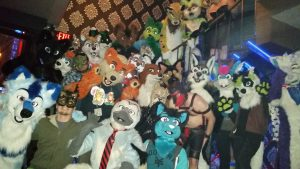 Fursuiters and revelers alike standing on the stairs at Long Beach's Executive Suite