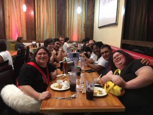 Furries smiling for the camera while seated at the Redlands FurMeet