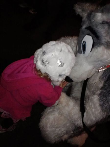 Closeup of child interacting with fursuiter at the Riverside Under the Lights meet