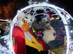 Gheyna, Coony and a white bird fursuiter sitting inside the Cinderella style carriage at Riverside's Under the Lights