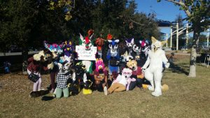 Group photo from Conejo Creek park, from summer of 2018. Kairin Rex holds a small banner for the furmeet.