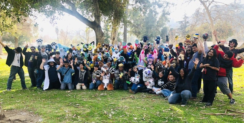 Group photo from February 2020's RBFM Furmeet. About 60 furs are gathered for this photograph. Some are standing, others are kneeling or sitting. Many attendees have their hands held out wide in greeting. Photo by Renn.