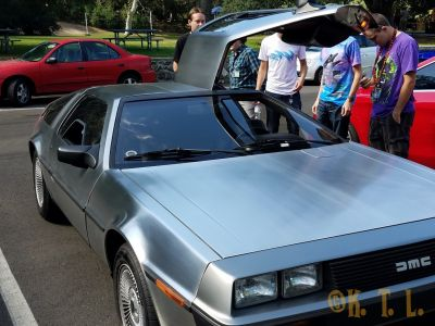 DeLorean car being admired in the parking lot