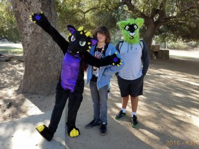 Dragon fursuiter standing with friend and green wolf