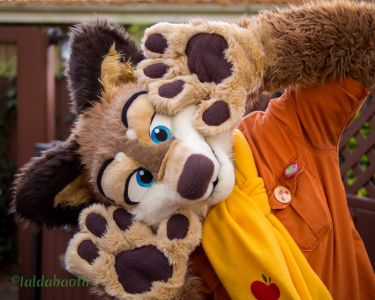 Brownwolf wearing a scarf and making a face and hand gesture at the camera