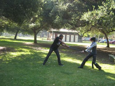 2 attendees sparring with wooden foam weapons