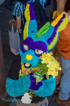 Fursuiter holding a prop of flowers in the crowd