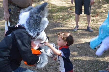 AceofHeartsFox crouched down to interact with a young child. photo courtesy PonyQuest