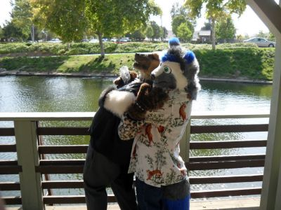 Friends standing on the deck at the river, hugging it out